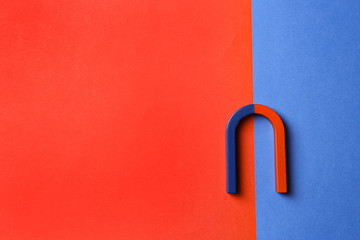 Red and blue horseshoe magnet on color background, top view. Space for text