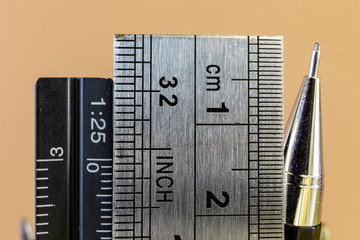 Rulers and mechanical pencil macro image in yellow background. High quality steel technical drawing tools with different measuring scales.