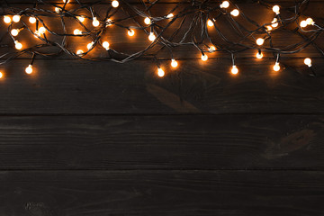 Glowing Christmas lights on dark wooden background, top view. Space for text
