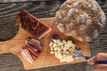 Snack with delicious South Tyrolean smoked bacon and cheese with flat bread lying on a rustic table