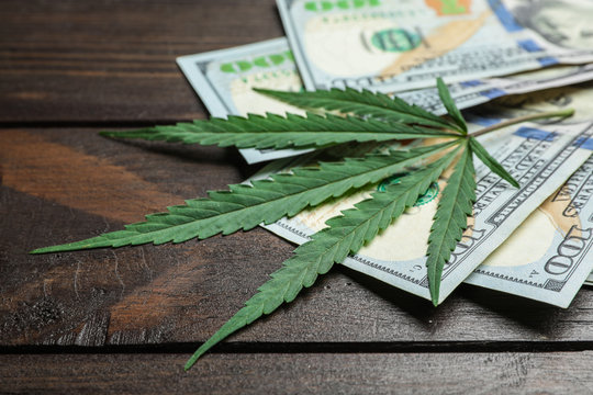 Hemp leaf and dollars on wooden background, closeup