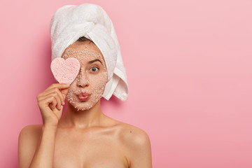 Fototapeta Reducing pores and cleansing concept. Attractive female applies sea salt mask on face, has luxurious feelings from beauty treatments, covers eye with heart shaped sponge, pampers complexion. obraz