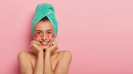 Facial care and beauty concept. Glad young woman keeps hands under chin, looks happily at camera, has toothy smile, smooth healthy skin, applies pads for rejuvenation, isolated on pink wall.