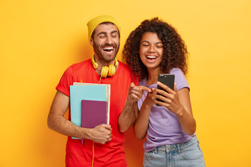 Happy diverse students look happily at smartphone device, hold notepad, wear stylish bright clothes, isolated over yellow background surf internet glad to read funny message content. Youth, technology