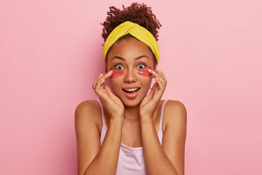 Surprised dark skinned curly young woman with collagen patches under eyes, looks impressively at camera, wonders awesome rejuvenating effect of beauty product, wears yellow headband and t shirt.