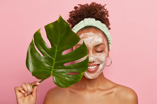 Portrait of happy African American woman covers half of face with green leaf, cleans face, washes with bubble soap, stands topless, cares aboout her beauty and body, isolated over pink background