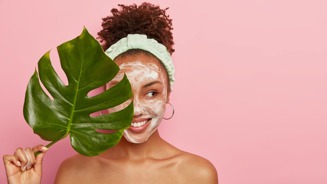 Pleased dark skinned woman stands naked alone, looks aside with cheerful expression, holds green leaf near face, expresses good emotions, enjoys softness from washing face, wears headband, earrings