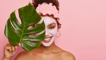 Cheerful beautiful African American model wears facial clay mask for looking younger, wears...