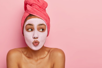 Indoor shot of good looking dark skinned model makes lips folded as if wanting to kiss someone, wears nourishing clay mask, wrapped in towel, looks aside on blank space, isolated on pink wall