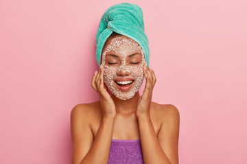 Positive young lady massages face with special scrub, reduces dark dots on cheeks, feels pleasure from beauty treatments, has skin problem, cares about hair, wrapped in towel. High resolution
