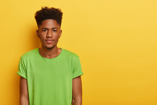 Photo of handsome teenage boy with dark skin, curly hairstyle, wears casual green t shirt, looks with calm serious expression at camera, isolated over yellow background, blank space on right side