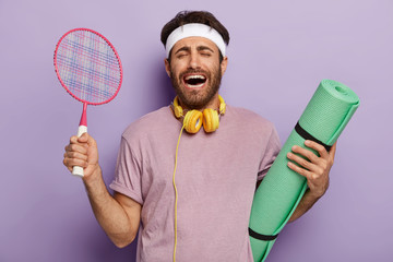Emotional sporty man trains with fitness mat and tennis racket, laughs with overjoyed expression, has dark hair, dressed in casual wear, listens music during training, isolated over purple background.