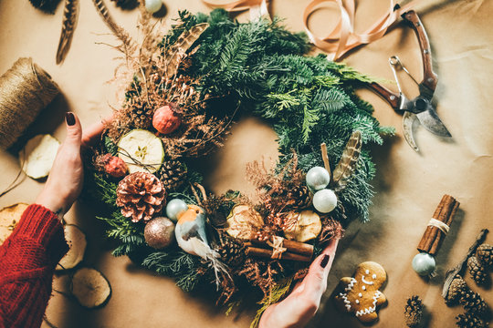 Top view Christmas wreath on craft background, pretty famales hands decorate christmas wreath.