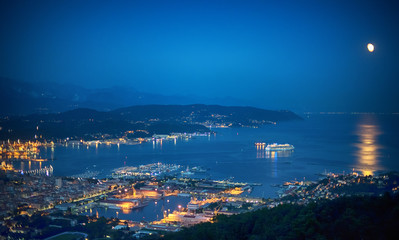 Fotobehang Liguria Illuminated cruise ship in La Spezia Gulf at dusk