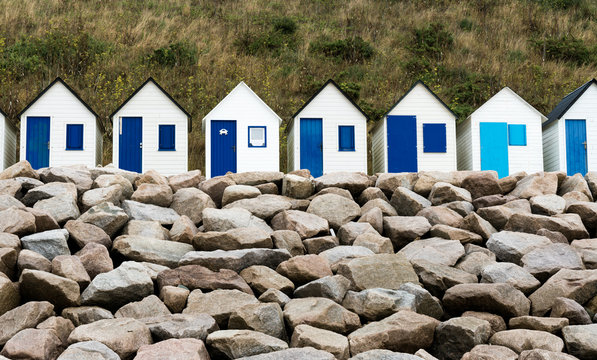 row of small wooden beach cottages on the rocky Normandy coast