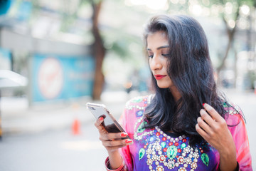 Young South Asian Woman using her mobile phone