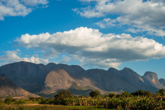 A mountain range rises up over lush green vegetation in Mozambique, Africa