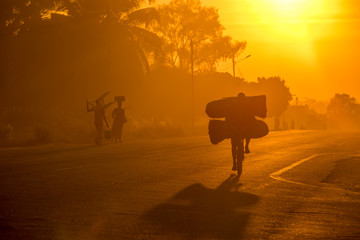 A Mozambican cyclist carrying large bags of coal to market at sunrise in the morning, along a tarmac road. Other commuters carrying items in the background. Nampula Town, Mozambique