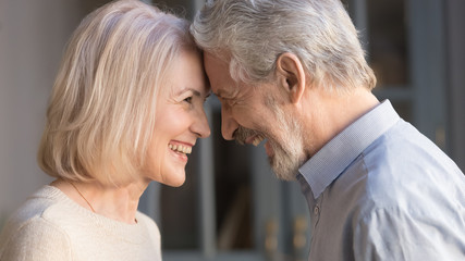 Happy mature couple touch foreheads enjoying romantic moment