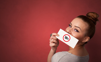 Young person holding adult content card in hand