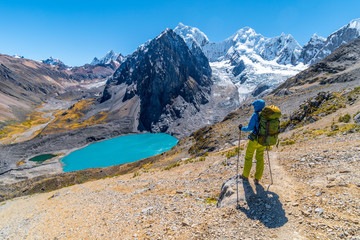 Girl hiking by stunning lake Juraucocha, San Antonio pass with view to Siula Grande peak, Huayhuash range, Huaraz, Ancash, Peru