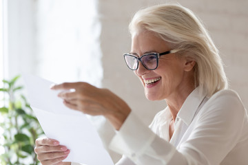 Happy senior woman read good news in paperwork document