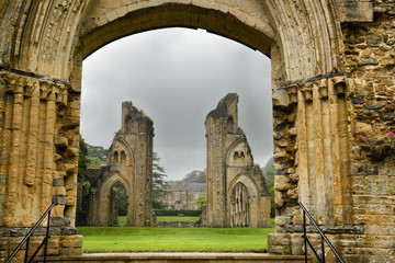 View of Abbey House and ruins of the Great Church from Lady Chapel at Glastonbury Abbey monastery in pouring rain in Glastonbury England