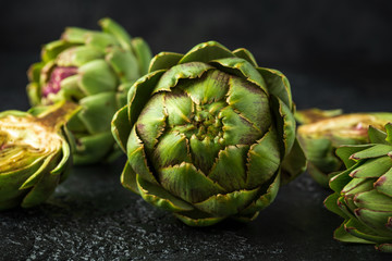 Fresh raw organically grown artichoke flower buds on dark background