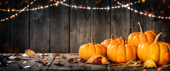 Thanksgiving Pumpkins And Leaves On Rustic Wooden Table With Lights And Bokeh On Wood Background - Thanksgiving / Harvest Concept