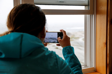 Megan Woodhouse takes a photograph using her phone from inside the Sou'Wester Gift Shop during the arrival of Hurricane Dorian in Peggy's Cove