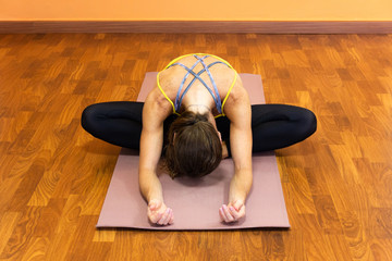 Woman on mat in butterfly pose with forehead forward at yoga studio. Female yogi on baddha konasana Restorative yin yoga exercise, flexibility concepts