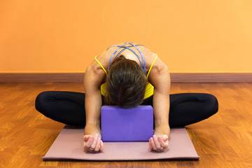 Woman in butterfly yin yoga asana with forehead resting on purple prop. Female yogi on baddha konasana pose on wooden plank floor studio. Relax exercise, flexibility concepts