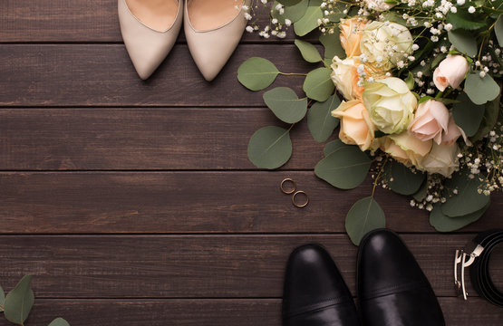 Bride groom shoes and roses bouquet on wooden floor