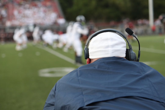 A high school football coach watches the line of scrimmage