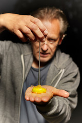 Egg yolk falling from hand to man hand palm