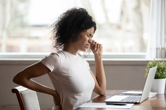 Hurt biracial woman work at laptop suffer from spinal spasm