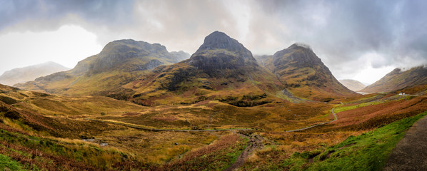 Panoramic view of steep mountains in the center and valleys on both sides with bright green and orange on an overcast afternoon in Glencoe, Highland, Scotland, United Kingdom