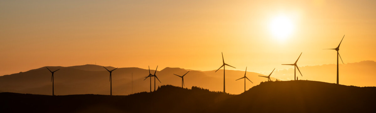 A windfarm with wind turbines at Planalto dos Graminhais in a poetic sunset setting, serving as a perfect image for green sustainable renewable engery.