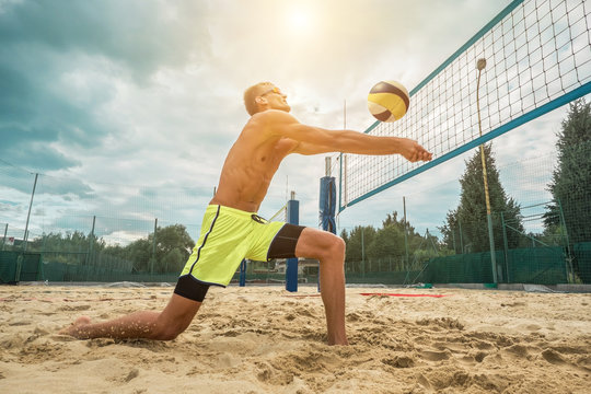 Beach Volleyball player in sunglasses in action with ball under