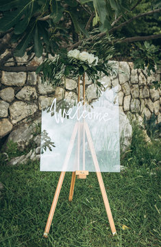 An easel decorated with flowers at a wedding event at which the inscription is welcome.