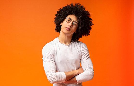 Skeptical black millennial man, looking suspiciously at camera