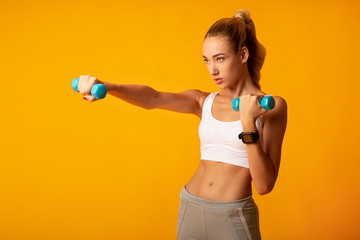 Young Woman Doing Dumbbell Boxing Workout On Yellow Background