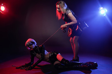 couple of lovers have fetish play in neon light on black background. woman mistress and her slim anime slave man in the studio.