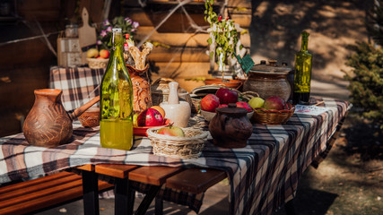 A laid table in a rustic style on the street. An exhibition of rustic interior. rural still life table. Still life with ripe apples and a bottle of moonshine