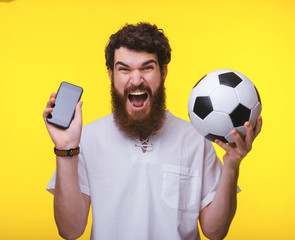 Photo of excited supporter, holding mobile and soccer ball over yelow background
