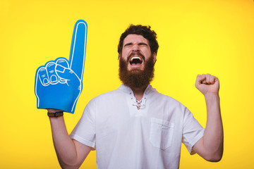 Photo of screaming supporter, with big blue finger glove, over yellow background