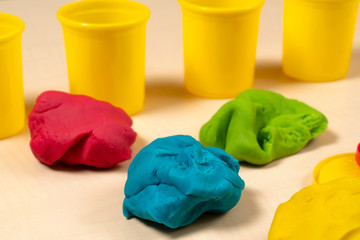 Green, blue, yellow and red play dough on wooden table