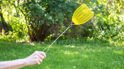 middle aged Caucasian female hand holding a yellow plastic fly swatter amid lush green trees with copy space