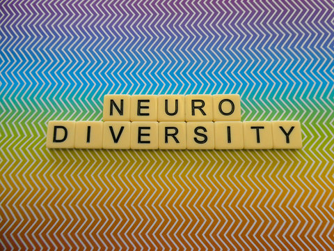"""Bright rainbow zig zag pattern background sign with the word """"NEURODIVERSITY"""" in text lettering, for a brilliant and eye catching sign or banner"""