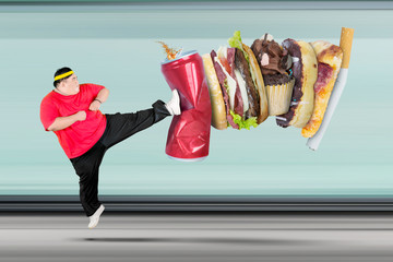 Overweight man kicking soft drink and fast food